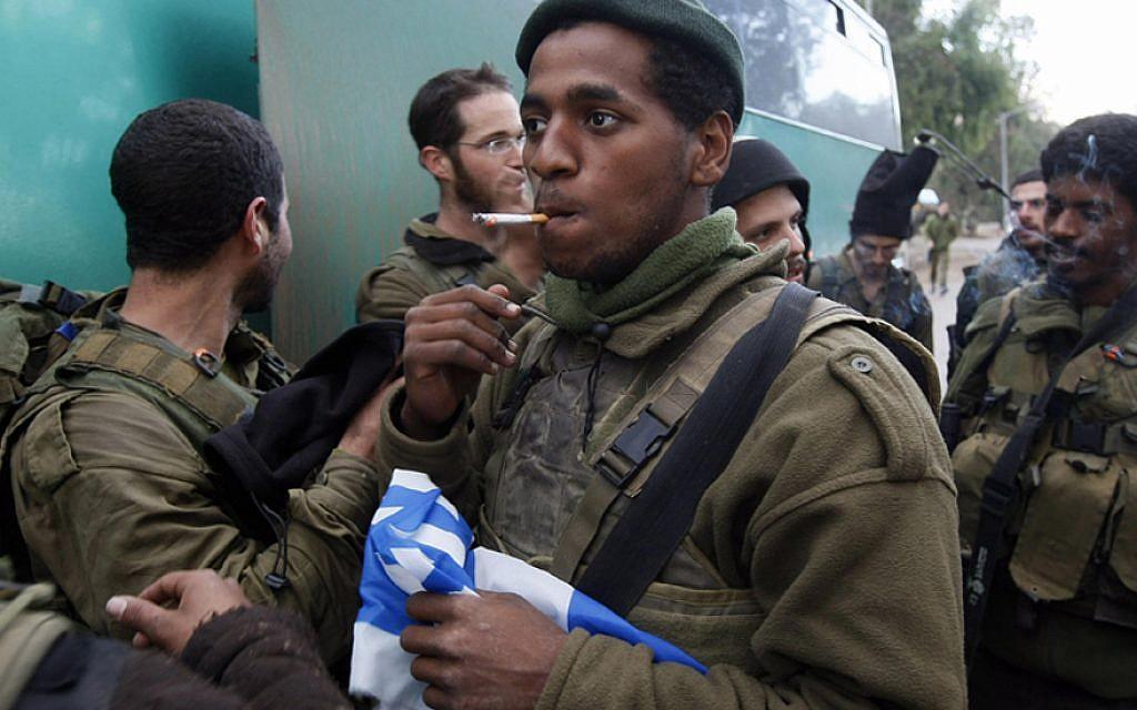 Un soldat israélien tient un drapeau national en fumant une cigarette près de la frontière Israël-Gaza après que son unité d'infanterie a quitté la bande de Gaza le 18 janvier 2009. (Menahem Kahana/AFP/Getty Images/via JTA)