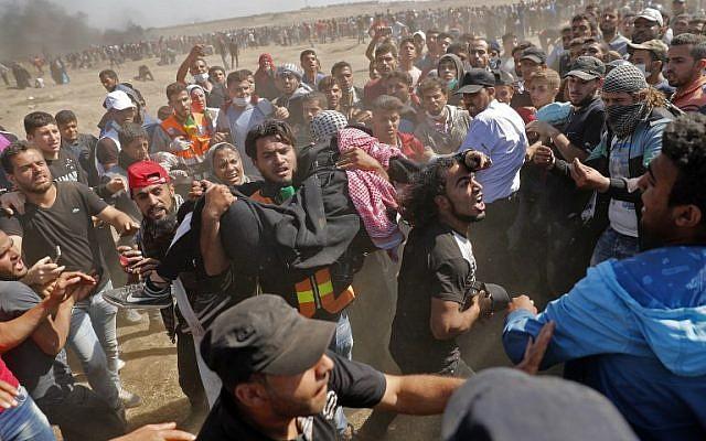 Des Palestiniens portent un manifestant blessé lors d'affrontements avec les forces israéliennes près de la frontière entre la bande de Gaza et Israël, à l'est de la ville de Gaza, le 14 mai 2018 (AFP PHOTO / Thomas COEX)