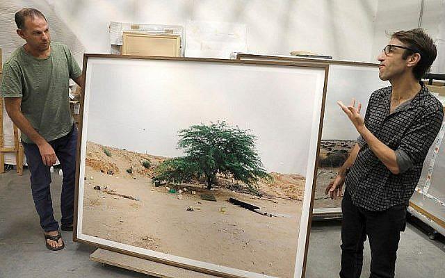 """L'artiste-photographe Ron Amir (à gauche) et le conservateur Noam Gal aux côtés d'une photographie de l'exposition """"Quelque part dans le désert"""", dans une salle du musée d'ISraël, en juillet 2018. (Crédit : AFP/Menahem Kahana)"""