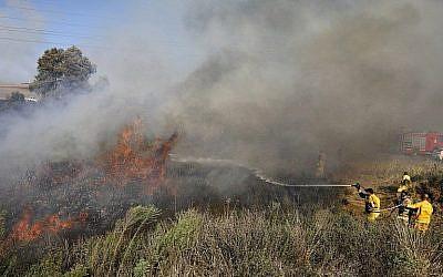 Les pompiers éteignent un incendie à proximité de Sdérot, dans le sud du pays, causé par un ballon incendiaire de la bande de Gaza, le 31 juillet 2018 (Crédit : AFP Photo/Menahem Kahana)