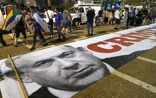 """Une bannière avec un message politique et une photo du Premier ministre  Benjamin Netanyahu sur le sol alors que les membres de la communauté druze et leurs soutiens manifestent contre la loi sur l'Etat-nation à Tel Aviv, le 4 août 2018. Le message   est """"Ministre du crime"""" (Crédit : AFP PHOTO / JACK GUEZ)"""