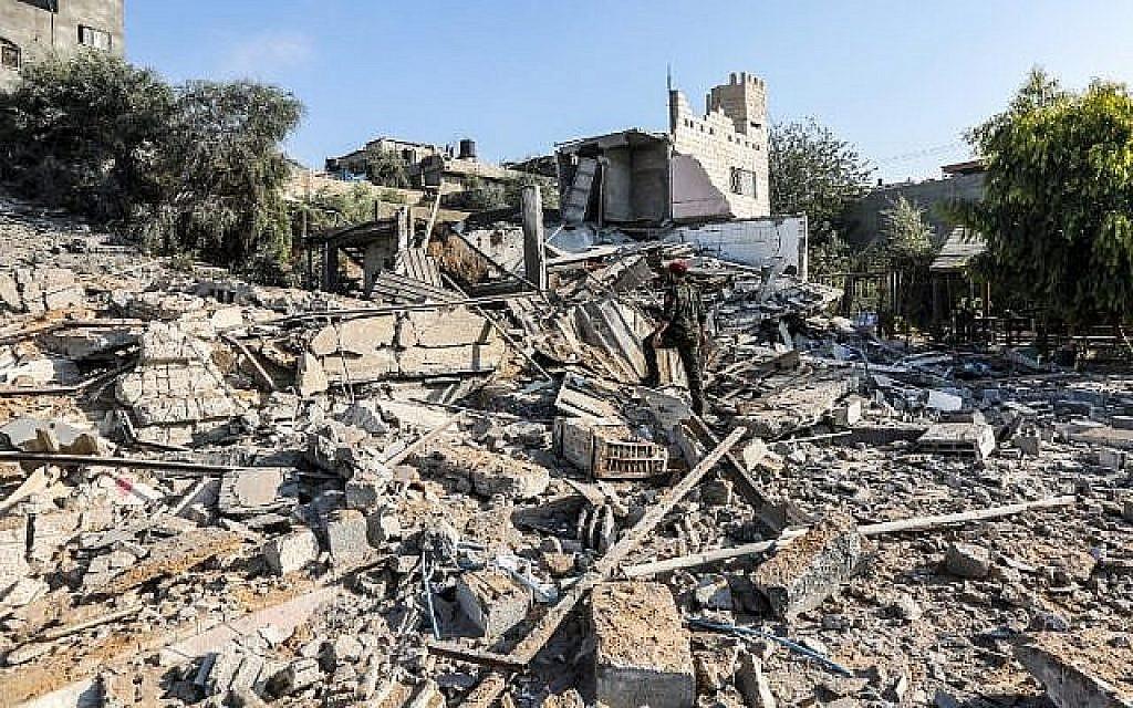 Un membre du Hamas traverse les décombres d'un site touché par des frappes aériennes israéliennes dans la ville de Gaza, le 9 août 2018 (Crédit : AFP / MAHMUD HAMS)