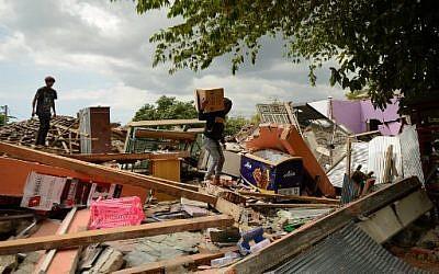 Un jeune homme récupère ses effets personnels alors qu'il grimpe sur les débris d'une maison effondrée à Kayangan, au nord de l'île de Lombok, le 9 août 2018, à la suite du séisme du 5 août. (Crédit : SONNY TUMBELAKA / AFP)