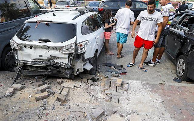 Des hommes israéliens se tiennent à côté d'une voiture qui a été endommagée après qu'une roquette tirée par des terroristes de la bande de Gaza soit tombée dans la ville de Sderot, dans le sud d'Israël, le 9 août 2018. (AFP PHOTO / JACK GUEZ)