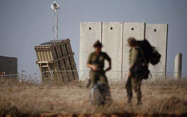 Des soldats israéliens marchent près d'un système de défense Iron Dome, conçu pour intercepter et détruire les roquettes à courte portée et les obus d'artillerie, dans la ville de Sderot, dans le sud d'Israël, le 9 août 2018. (Crédit : AFP PHOTO / Jack GUEZ)