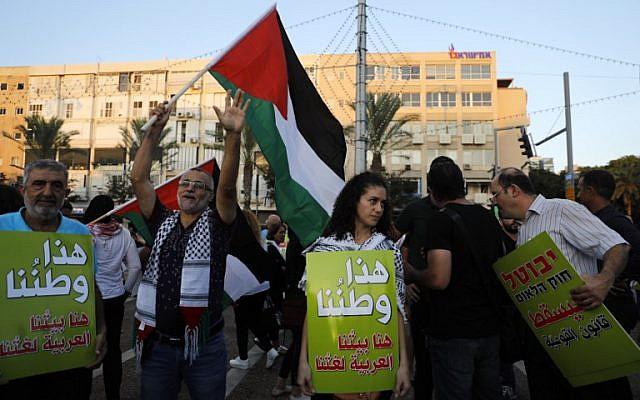 """Les manifestants portent des banderoles lors d'une manifestation de protestation contre la loi de l'État-nation à Tel-Aviv le 11 août 2018. Sur les bannières en arabe: """" C'est notre nation, c'est notre maison, l'arabe est notre langue """". (AFP/Ahmad GHARABLI)"""