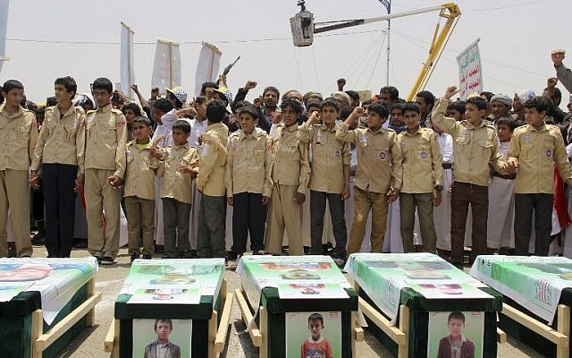 Des enfants yéménites expriment leur colère contre Riyad et Washington alors qu'ils participent à des funérailles massives d'enfants tués dans une frappe aérienne la semaine précédente par une coalition dirigée par les Saoudiens, ici dans la ville de Saada, au nord du Yémen, le 13 août 2018. (AFP)