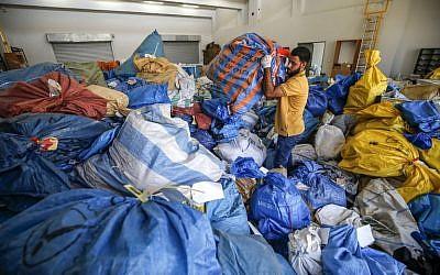 Un employé palestinien des services postaux trie les sacs de courrier qui n'a pas été livré depuis 2010, à Jéricho, en Cisjordanie, le 14 août 2018. (Crédit : AFP / ABBAS MOMANI)