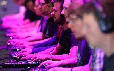 Des visiteurs testent jeux vidéos au Gamescom de Cologne, le 22 août 2018. (Crédit : AFP PHOTO / dpa / Oliver Berg / Germany OUT)