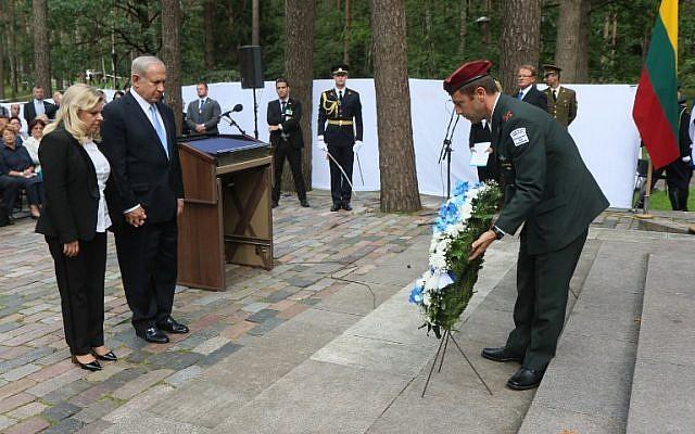 Le Premier ministre israélien Israel Benjamin Netanyahu et son épouse Sara se recueillent durant une cérémonie de dépose de gerbe au mémorial de la Shoah de Paneriai, à proximité de Vilnius, le 24 août 2018 (Crédit :/ AFP PHOTO / Petras Malukas)