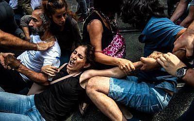 La police anti-émeutes maintient au sol des manifestants lors d'un mouvement de protestation d'un groupe de mères, samedi, le 25 août 2018 à Istanbul (Crédit : AFP/Yasin AKGUL)