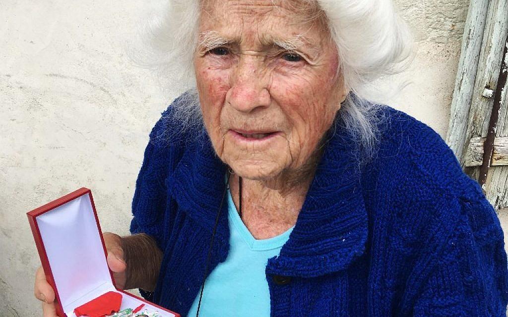 Genevieve Callerot, 102 ans pose avec sa Légion d'honneur dans le jardin de sa ferme, à Saint-Aulaye, dans le sud-ouest de la France, le 25 août 2018 (Crédit : AFP / MEHDI FEDOUACH)