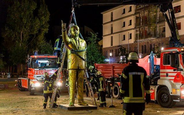 Des employés municipaux déboulonnent une statue de Recep Tayyip Erdogan, le 29 août à Wiesbaden, en Allemagne. (Crédit : AFP / dpa / Sebastian Stenzel / Germany OUT)
