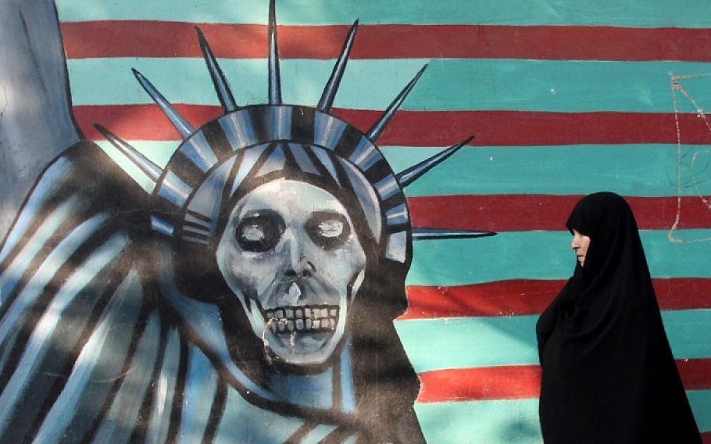 Une Iranienne promène son chien devant une fresque sur le mur de l'ancienne ambassade américaine à Téhéran, le 9 novembre 2016. (Crédit : AFP/Atta Kenare)