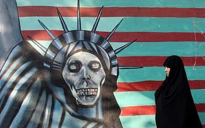 Une Iranienne promène son chien devant une fresque sur le mur de l'ancienne ambassade américaine à Téhéran, le 9 novembre 2016 (Crédit : AFP/Atta Kenare)