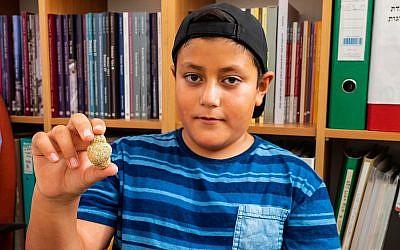 Itamar Barnea, 10 ans, avec une figurine de 11 500 ans trouvée en haute-Galilée en 2016. Une photo prise en août  2018. (Crédit : Assaf Peretz/Israel Antiquities Authority)