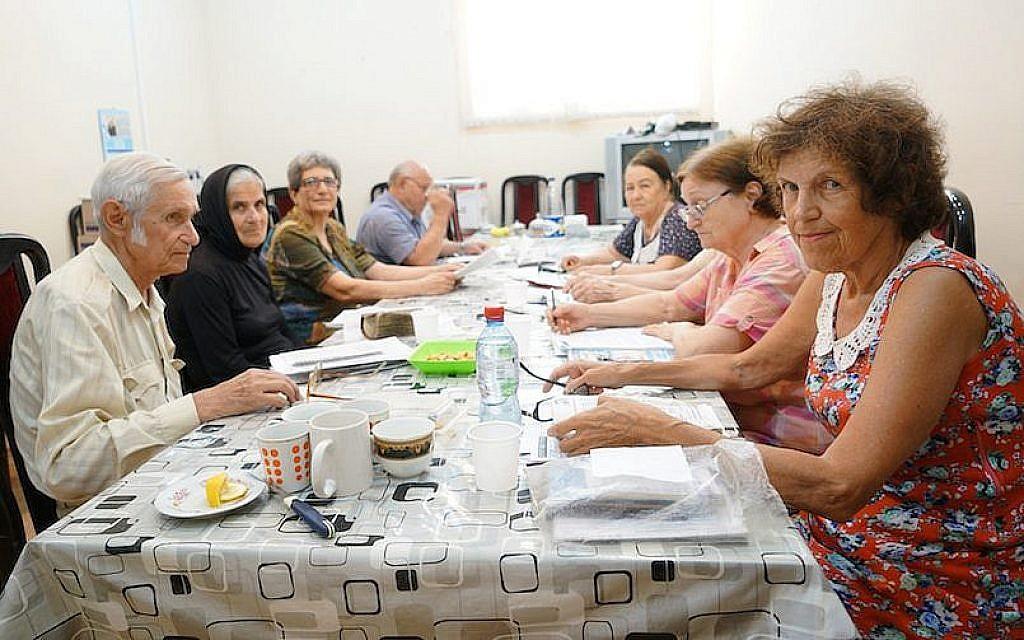 Arnold Zeligman, à gauche, apprend l'hébreu à Bella Regimov, qui porte un foulard, et aux autres élèves de la Maison juive de Bakou, en Azerbaïdjan, le 18 juillet 2018 (Crédit : Cnaan Liphshiz/JTA)
