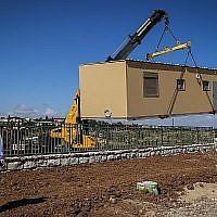 Image d'illustration : une grue installe un bungalow dans la nouvelle implantation d'Etzion, en Cisjordanie, destinée à réinstaller les évacués de l'avant-poste de Netiv Ha'avot, le 9 mai 2018. (Gershon Elinson / Flash90)