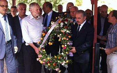 Jeremy Corbyn porte une gerbe de fleurs durant une visite aux Martyrs de Palestine, en Tunisie, en octobre 2014. (Crédit : page Facebook officielle de l'ambassade palestinienne en Tunisie)