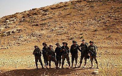"""Des soldats posent après avoir """"conquis"""" une colline dans le cadre d'un exercice d'entraînement dans la vallée du Jourdain le 28 novembre 2017. (Judah Ari Gross/Times of Israel)"""