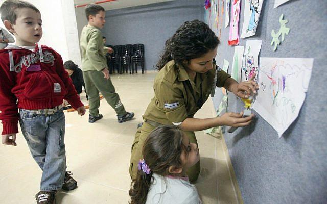 Illustration d' un soldat de l'armée israélienne jouant avec des enfants dans un abri anti-aérien dans le sud d'Israël en novembre 2012. (Miriam Alster / Flash 90)