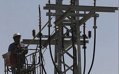 Image illustrant un employé de Israël Electricity Corporation soulevé par une grue au niveau d'un poteau de services publics pour effectuer des travaux de maintenance le 10 juin 2013. (Flash 90)