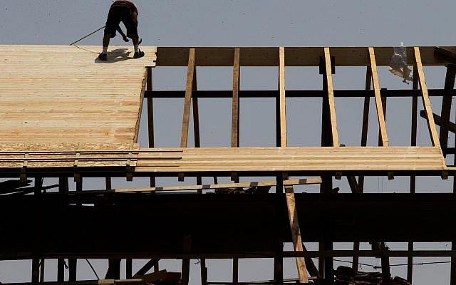 Un ouvrier travaille sur un toit d'un chantier de construction à Jérusalem, le 5 août 2015 (Nati Shohat/Flash90).