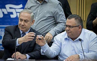 Le Premier ministre Benjamin Netanyahu, à gauche, et David Bitan partageant un toast lors d'une réunion de faction du Likoud le 27 février 2017. (Yonatan Sindel / Flash90)