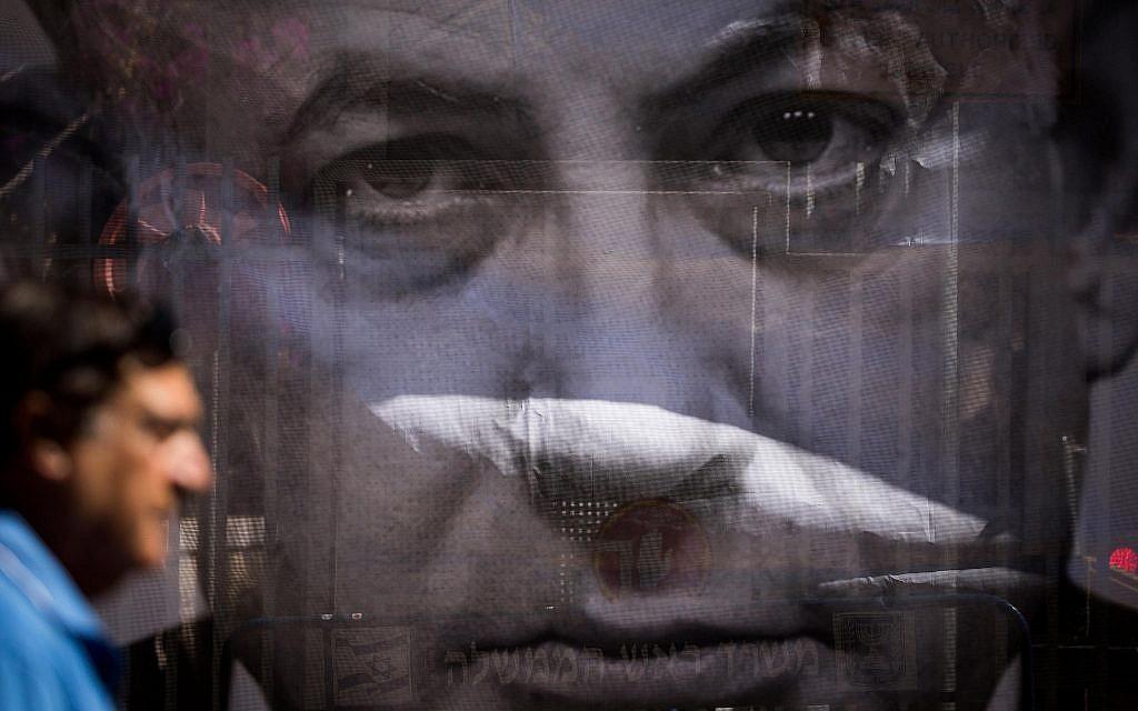 Un homme passe devant une affiche critiquant le Premier ministre Benjamin Netanyahu près de sa résidence à Jérusalem, alors que les enquêteurs de la police arrivent pour l'interroger sur des allégations de corruption, le 10 juillet 2018. (Yonatan Sindel/Flash90)