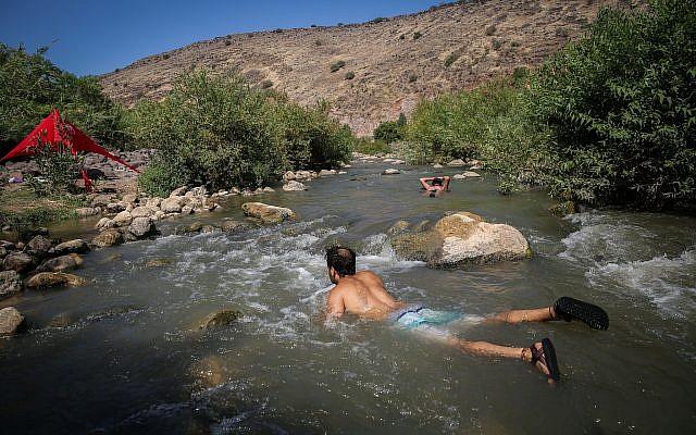 De jeunes Israéliens se rafraîchissent dans une rivière du plateau du Golan, dans le nord d'Israël, le 10 aout 2018 (Crédit : David Cohen/Flash90)