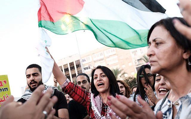 """Arabes Israéliens , certains brandissant des drapeaux palestiniens, protestent contre la """"loi de l'État-nation"""" sur la place Rabin à Tel-Aviv le 11 août 2018. (Tomer Neuberg/Flash90)"""