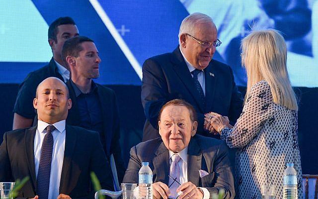 L'homme d'affaires et investisseur Sheldon Adelson, assis sur la droite, son épouse  Miriam avec le président Reuven Rivlin , débout, au milieu, et le ministre de l'Education Naftali Bennett, à gauche, lors de l'inauguration de la faculté de médecine de l'université d'Ariel en Cisjordanie, le 19 août 2018 (Crédit :Ben Dori/Flash90)