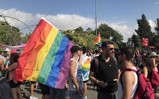 Les participants se rassemblent pour le défilé annuel de la gay pride à Jérusalem, le 2 août 2018. (Crédit : Luke Tress / Times of Israel)