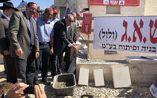 L'ancien gouverneur de l'Arkansas Mike Huckabee pose des briques  lors d'une cérémonie organisée dans un nouveau complexe de logements au sein de l'implantation d'Efrat, en Cisjordanie, le 1er août 2018 (Crédit : Jacob Magid/Times of Israel)