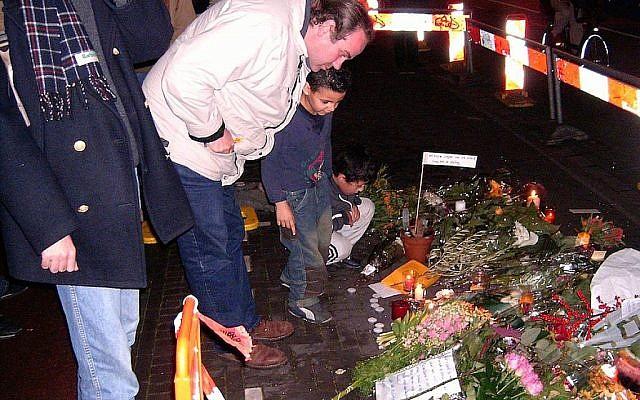 Les visiteurs d'un mémorial de fortune qui marque l'endroit où le cinéaste Theo van Gogh a été assassiné à Amsterdam, le 2 novembre 2004. (Crédit : Wikimedia Commons / via JTA)