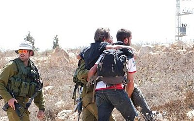 Un militant de gauche escorté par l'armée israélienne à proximité de l'implantation de Mitzpeh Yair, en Cisjordanie, le 25 août 2018 (Crédit : BTselem)