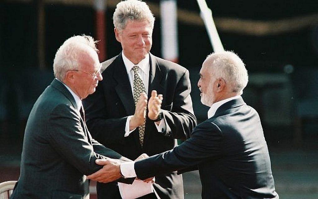 Le Premier ministre israélien Yitzhak Rabin (à gauche) serre la main du roi Hussein de Jordanie sous les applaudissements du président des Etats-Unis Bill Clinton lors de la signature du traité de paix bilatéral, octobre 1994 (photo : Nati Shohat/Flash90).