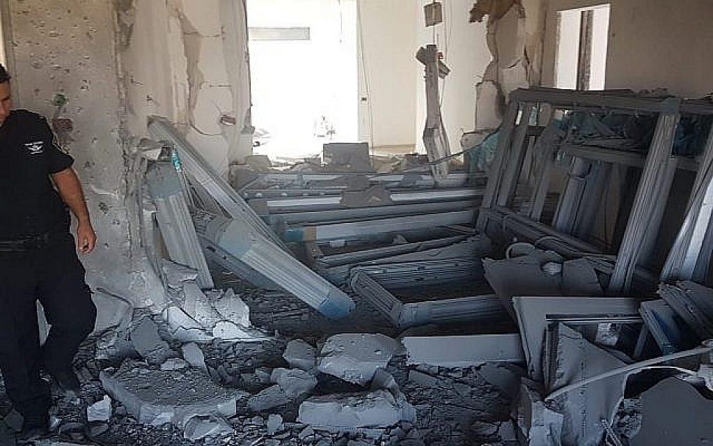 Un officier de police inspecte les dégâts sur un chantier de construction dans la ville de Sdérot, au sud d'Israël, près de la frontière de Gaza, suite à une salve de roquettes, le 9 août 2018. (Crédit : Police israélienne)