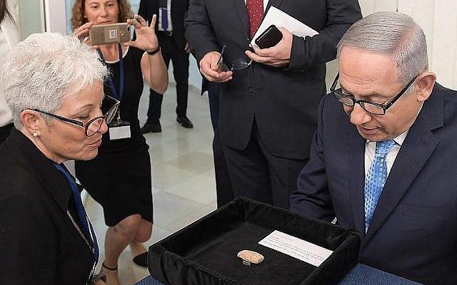 """Le Premier ministre Benjamin Netanyahu et Amanda Weiss, directrice du Musée des terres bibliques à Jérusalem, avec une tablette d'argile vieille de 2 600 ans portant le nom de """"Benayahu ben Netanyahu"""" prêtée au Bureau du Premier ministre pour l'année prochaine, le 21 août 2018 (Crédit : GPO)"""