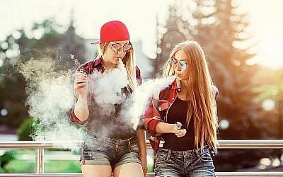 Image illustrative de deux femmes en train de vapoter à l'extérieur. (iStock par Getty Images/licsiren)