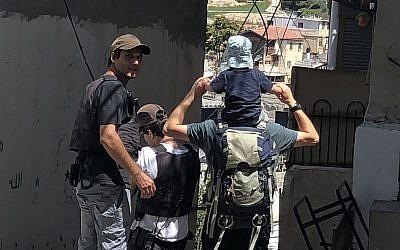 Des gardes de sécurité privés financés par l'Etat escortent une famille juive à la maison Beit Rachel, appartenant à Ateret Cohanim dans le quartier de Batan al-Hawa de Silwan, à Jérusalem Est, le 31 juillet 2018 (Crédit : Sue Surkes/Times of Israel.)