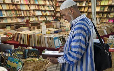 Un client consulte des livres dans une librairie de la capitale marocaine de Rabat, le 9 août 2018. Sur les principales artères du vieux Rabat, des dizaines de libraires itinérants proposent des livres en français, en arabe et parfois en anglais, jusqu'à dix fois moins chers que leurs originaux. (AFP PHOTO / FADEL SENNA)