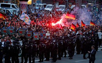 Des manifestants de droite allument des fusées le 27 août 2018 à Chemnitz, dans l'est de l'Allemagne, suite à la mort d'un Allemand de 35 ans qui aurait été tués par deux migrants du monde musulman (Crédit : AFP Photo/Odd Andersen)