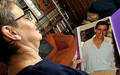 Leah Goldin (L), the mother of Israeli soldier Lieutenant Hadar Goldin, holds up a picture of her son as she speaks during an interview with AFP at their family home in the central Israeli city of Kfar Saba on August 29, 2018. From the living room of their home in central Israel, surrounded by books and family photos, Leah and Simha Goldin have waged a years-long campaign to bring back the remains of their son, Lieutenant Hadar Goldin, a soldier killed in the 2014 Gaza war, and whose body is believed to be held by Hamas. / AFP PHOTO / JACK GUEZ