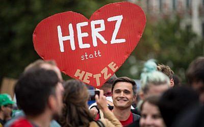 """Un manifestant tient une pancarte """"le coeur, pas les agitations"""" durant un contre-rassemblement contre une marche organisée par le parti d'extrême droite de l'AfD et le parti Pegida à Chemnitz, en Allemagne, le 1er septembre (Crédit :   / AFP PHOTO / dpa / Monika Skolimowska / Germany OUT)"""