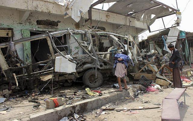 Les Yéménites réunis autour d'un bus détruit sur le site d'une frappe aérienne de la coalition menée par les saoudiens qui a visé le marché de Dahyan la veille dans la province de Saada, bastion des Houthis, le 10 août 2018 (Crédit : AFP PHOTO / -)