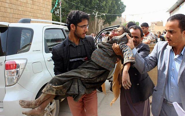 Un enfant yéménite emporté vers un hôpital après avoir été blessé lors d'une attaque aérienne présumée contre le bastion des Houthis soutenus par Iran dans la province de Saada, le 9 août 2018 (Crédit :  AFP)