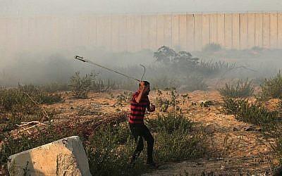 Un Palestinien utilise une fronde pour lancer une pierre contre un soldat israélien, près du point de passage d'Erez, à Gaza, le 4 septembre 2018. (Crédt : AFP/Mahmud HAMS)