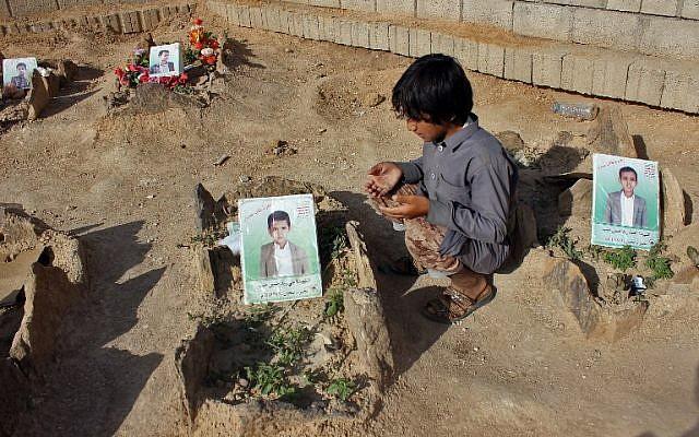 Un petit yéménite fait une prière près des tombes des enfants tués lorsqu'un bus a été touché par une frappe aérienne dirigée par les saoudiens  qui a visé le marché de Dahyan la veille dans la province de Saada, bastion des Houthis, photo prise le 4 septembre 2018 (Crédit : AFP PHOTO / STRINGER)
