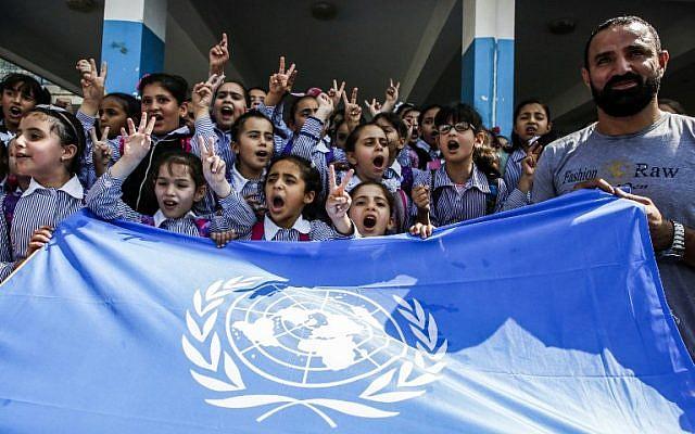 """Des écoliers palestiniens chantent des slogans et font le signe de la victoire devant le drapeau de l'ONU lors d'une manifestation organisée le 5 septembre 2018 dans le camp de réfugiés d'Arroub, près de Hébron, en Cisjordanie, dans une école financée par les États-Unis, qui a été construite sous les auspices de l'UNRWA (United Nations Relief and Works Agency - UNRWA). Les Etats-Unis, premier contributeur de l'UNRWA, ont annoncé le 31 août qu'ils mettaient fin à tout financement de l'organisation, qu'ils ont qualifié de """"irrémédiablement défectueuse"""" (Crédit : AFP PHOTO / HAZEM BADER)"""